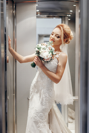 stylish blonde bride with modern bouquet posing in elevator in the morning in hotel. wedding day concept. beautiful woman in white dress with flowers Stockfoto - 99528635