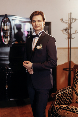 stylish groom in bow tie and blue suit getting ready in the morning in hotel, looking in mirror. wedding day concept. handsome man preparations in vintage room, in tuxedo with boutonniere