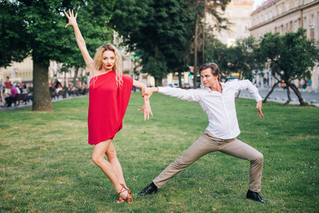 beautiful happy couple in love embracing and dancing in sunny street. stylish hipster groom and blonde bride performing dance, professional dancers. romantic moments in summer