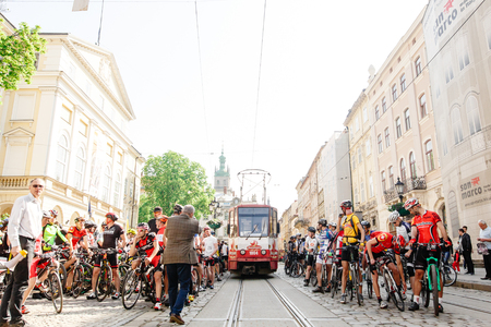 Lviv, Ukraine - May 6, 2017: cycling marathon VIII Lviv 100km ride, 425 bicycles, in the streets of the city. participants and athletes riding bikes and waiting for tram to pass