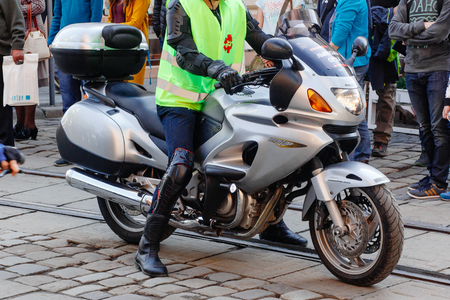 Lviv, Ukraine - May 6, 2017: cycling marathon VIII Lviv 100km ride, 425 bicycles, in the streets of the city. brutal man in leather jacket on stylish motor bike, participants  riding bikes