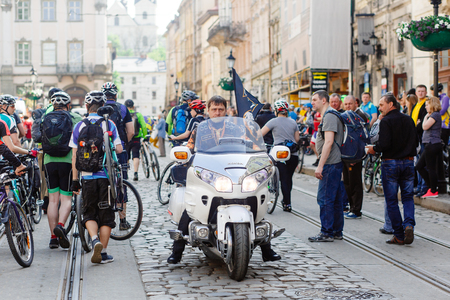 Lviv, Ukraine - May 6, 2017: cycling marathon VIII Lviv 100km ride, 425 bicycles, in the streets of the city. brutal man on stylish steel vintage motor bike, participants and athletes riding bikes
