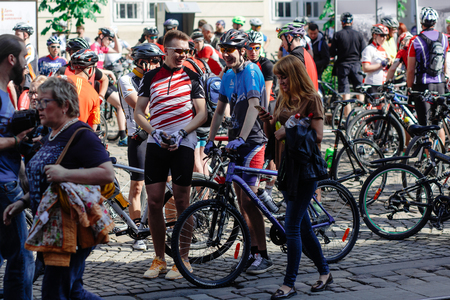 Lviv, Ukraine - May 6, 2017: cycling marathon VIII Lviv 100km ride, 425 bicycles, in the streets of the city. participants and athletes riding bikes. girl looking at phone