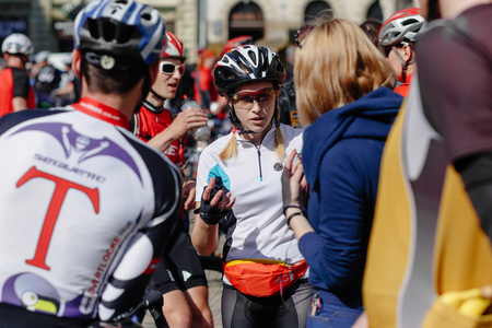 Lviv, Ukraine - May 6, 2017: cycling marathon VIII Lviv 100km ride, 425 bicycles, in the streets of the city. participants and athletes riding bikes. woman talking