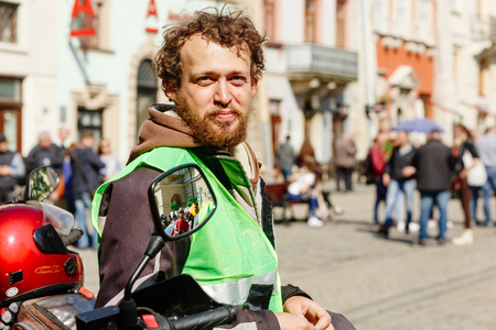 Lviv, Ukraine - May 6, 2017: cycling marathon VIII Lviv 100km ride, 425 bicycles, in the streets of the city. participants and athletes riding bikes. funny mean with beard smiling
