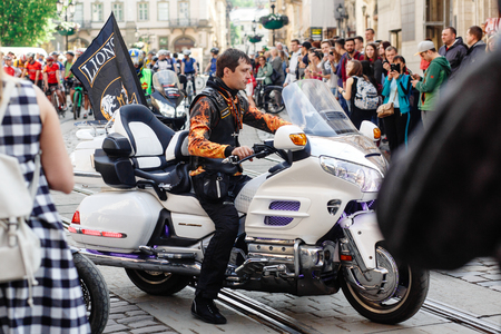 Lviv, Ukraine - May 6, 2017: cycling marathon VIII Lviv 100km ride,  in the streets of the city. brutal man in leather jacket on stylish motor bike, participants  riding bikes, ukraine lions