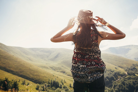 stylish traveler girl in hat with windy hair in light looking at sunny mountains. summer vacation. travel and wanderlust concept. space for text. back view. amazing atmospheric moment 스톡 콘텐츠