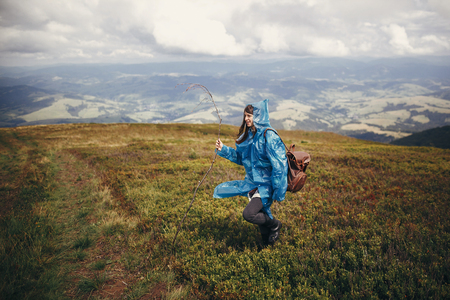 traveler hipster girl in blue raincoat with backpack, exploring misty mountains. space for text. atmospheric moment. travel and wanderlust concept.  woman walking on hills Stock Photo