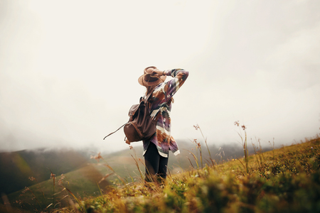 travel and wanderlust concept. stylish traveler hipster girl holding hat, with backpack and windy hair, walking in mountains in clouds. summer vacation. space for text. amazing atmospheric moment