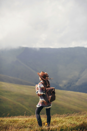 travel and wanderlust concept. traveler hipster girl in hat with backpack exploring misty sunny mountains in clouds. space for text. stylish woman traveling. amazing atmospheric moment.