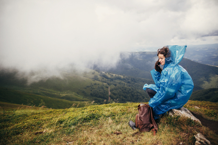 traveler hipster girl in blue raincoat with backpack, exploring misty mountains. space for text. atmospheric moment.  woman sitting on top hill. travel and wanderlust concept Stockfoto