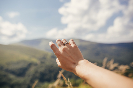 traveler hand reaching out to mountains with engagement ring. girl hand on background of sunny mountains and sky. travel and wanderlust concept. summer vacation