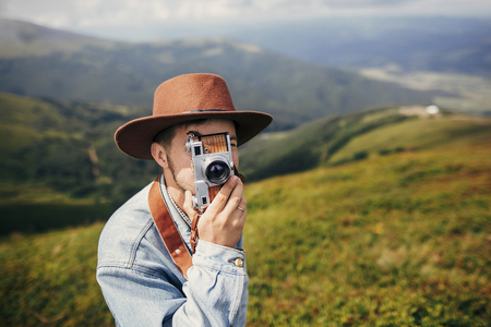stylish traveler man in hat taking photos on top of mountains with photo camera. space for text. hipster guy traveling, making images. amazing atmospheric moment. travel and wanderlust