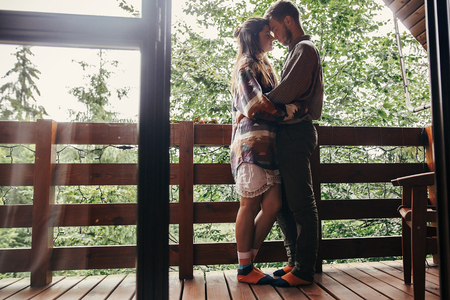 stylish hipster couple relaxing on porch, hugging in wooden cottage at woods in mountains. happy family embracing at home. summer vacation. atmospheric moment. Foto de archivo