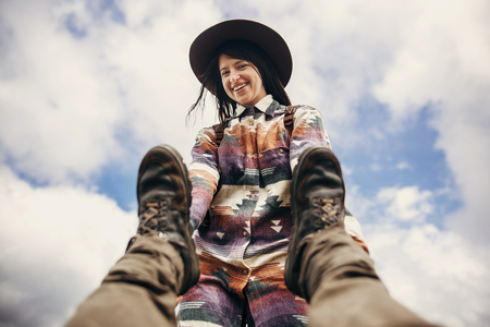 happy stylish traveler girl in hat holding man legs, and smiling, funny moment  of guy falling down on top of mountains. travel and wanderlust concept. space for text. couple traveling