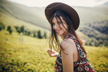 happy traveler hipster girl in hat, walking in sunny mountains. summer vacation. space for text. happy atmospheric moment. focus on hair. travel and wanderlust concept