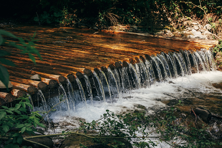 beautiful waterfall cascades on river in forest in mountains. river wooden dam. beautiful scenery landscape of river in woods under summer sun light