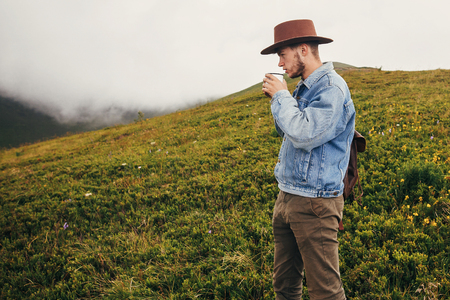 travel and wanderlust concept. stylish traveler man in hat with backpack holding cup of tea in mountains with clouds. space for text. hipster guy traveling. amazing atmospheric moment