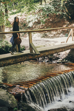 stylish traveler girl with hat walking at waterfall river in sunny forest. summer vacation. travel and wanderlust concept. space for text. back view. woman traveling in mountains