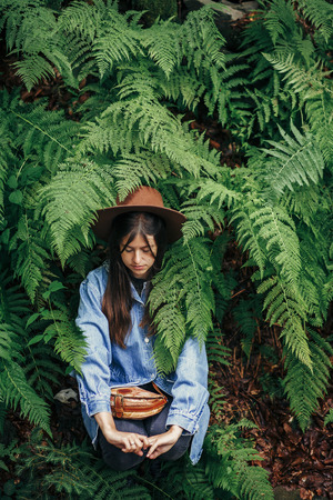 stylish hipster girl in hat sitting in fern bushes, among fern leaves in forest. creative portrait of woman traveler. environmental concept. travel and wanderlust concept. space for text Stockfoto