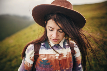 happy traveler hipster girl in hat with windy hair, relaxing in sunny mountains. space for text. atmospheric emotional moment. travel and wanderlust concept.  woman portrait