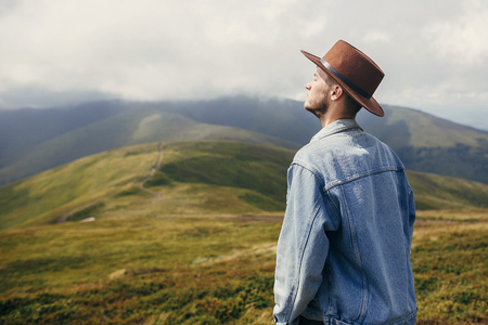 travel and wanderlust concept. stylish traveler man in hat standing on top of sunny mountains in clouds. space for text. hipster guy traveling on hills. amazing atmospheric moment.