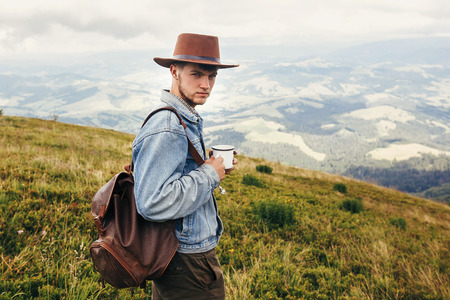 stylish traveler man in hat with backpack holding cup of tea in mountains with clouds. space for text. hipster guy traveling. amazing atmospheric moment. travel and wanderlust concept