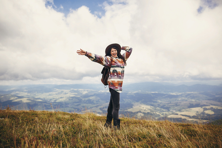 happy traveler hipster girl in hat, standing with backpack and smiling in mountains in clouds. space for text. amazing atmospheric emotional moment. travel and wanderlust concept