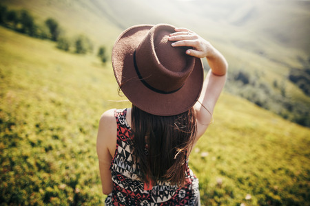 stylish traveler girl in hat with windy hair in light looking at sunny mountains. summer vacation. travel and wanderlust concept. space for text. back view. amazing atmospheric moment Imagens