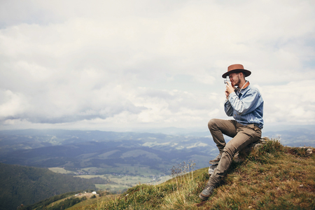 travel and wanderlust. stylish traveler man in hat sitting on top of  mountains with photo camera in clouds. space for text. hipster guy traveling, taking images. amazing atmospheric moment. Stock Photo