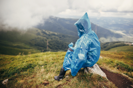 travel and wanderlust concept. traveler hipster girl in blue raincoat with backpack, exploring misty mountains. space for text. atmospheric moment.  woman sitting on top hill Stockfoto
