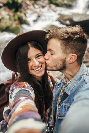 stylish hipster couple taking selfie and kissing at waterfall in forest in mountains. handsome man and happy woman in hat embracing on honeymoon. travel together. summer vacation