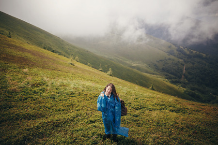 travel and wanderlust concept. traveler hipster girl in blue raincoat with backpack, exploring misty mountains. space for text. atmospheric moment.  woman walking on hills Stockfoto