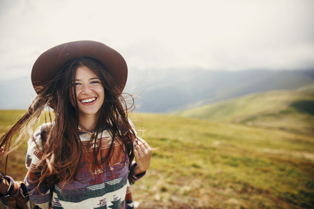 happy traveler hipster girl with windy hair  smiling, standing on top of sunny mountains. space for text. stylish woman in hat holding hair. atmospheric moment. travel and wanderlust Stock Photo
