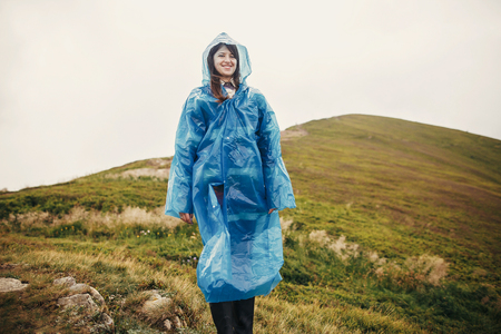 traveler hipster girl smiling in blue raincoat with backpack, exploring misty mountains. space for text. atmospheric moment. travel and wanderlust concept.  woman walking on hills