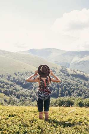 stylish traveler girl in hat looking at sunny mountains. summer vacation. travel and wanderlust concept. space for text. back view. woman traveling. amazing atmospheric moment