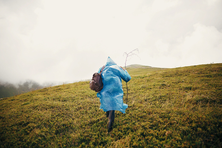 traveler hipster girl in blue raincoat with backpack, exploring misty mountains. space for text. atmospheric moment. travel and wanderlust concept.  woman walking on hills Stockfoto