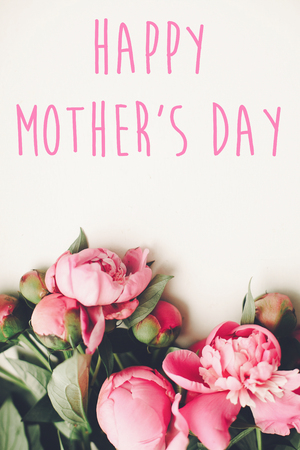 happy mothers day text on pink peonies bouquet on rustic white wooden background, top view. floral greeting card concept, flat lay. mothers day. vertical spring image Stock Photo