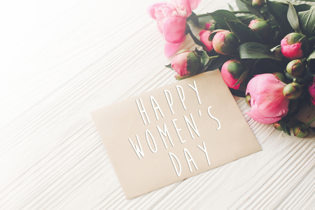 happy mothers day text on craft card and pink peonies bouquet on rustic white wooden background in light. floral greeting card concept, flat lay. mothers day. tender spring image