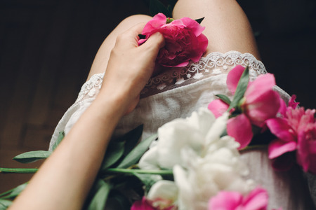 boho girl in white bohemia dress holding beautiful pink peonies on legs, top view. space for text. stylish hipster woman with flower in hand. moody morning. atmospheric sensual moment