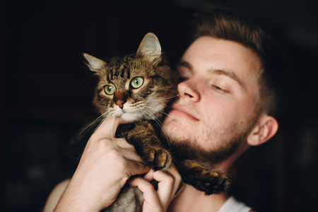 portrait of hipster man hugging his cute cat with amazing green eyes. funny maine coon and his owner playing together and hugging in room, sweet moments. adoption concept Stockfoto