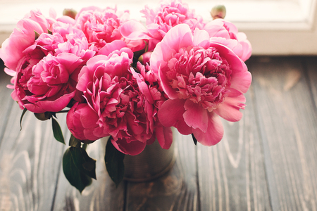lovely pink peonies bouquet on rustic dark wooden background at window light, space for text. top view. floral greeting card. happy mothers day. spring image. shabby chic concept