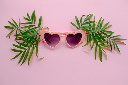 summer vacation concept. stylish pink sunglasses in heart shape and green palm leaves on pink background, flat lay. space for text.  time to travel concept and relax. holidays