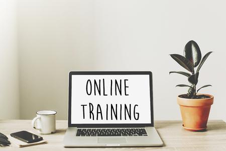 testo di formazione online sullo schermo del laptop sul desktop in legno con telefono, notebook, caffè e pianta. spazio di lavoro aziendale. concetto di formazione di Internet. e-learning