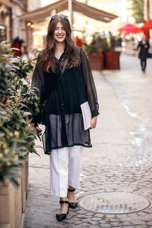 beautiful Hipster Girl in fashionable outfit, smiling and holding magazine in sunny street. happy stylish woman with gorgeous hair and smile, walking in sunlight in city