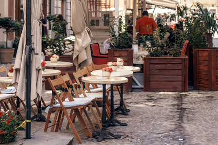 beautiful cafe terrace with little vintage tables and wooden chairs and plants, modern exterior of restaurant in european city street. food court in old city