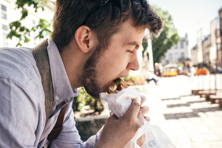 stylish hipster man eating delicious burger, sitting in city street. handsome guy biting and tasting yummy sandwich croissant in sunny street. fast food concept. space for text