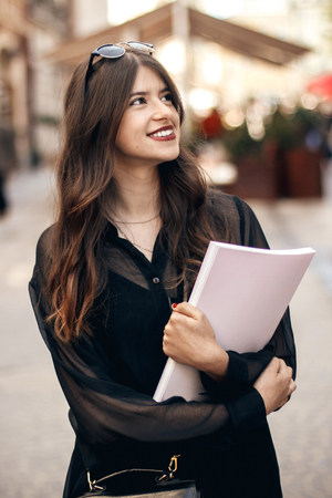 beautiful stylish hipster girl walking in sunny city street, holding magazine. happy gorgeous woman dressed in fashionable outfit, relaxing and enjoying time in european city