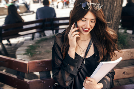 beautiful stylish woman sitting on bench in city street, holding phone and magazine. happy hipster girl in fashionable outfit, relaxing and talking on smartphone in european city Stockfoto