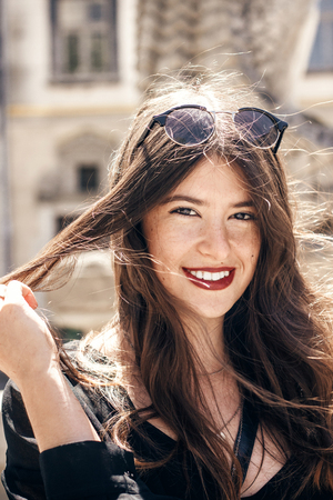 happy stylish woman with gorgeous smile and hair, posing in sunlight in city street. beautiful hipster girl in fashionable outfit, waving hair and smiling. luxury look.